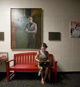 Student in costume studies in Randall Lobby.