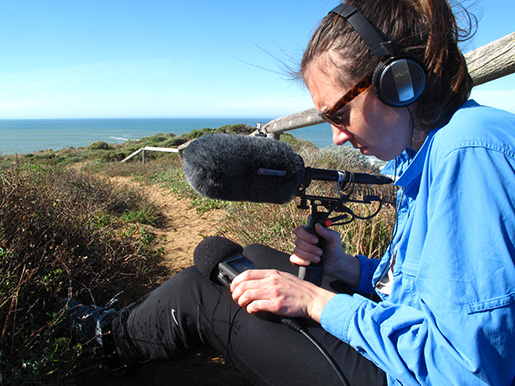 Student sitting on the beach with microphone and recorder