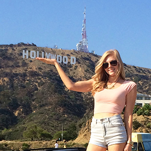 Girl standing in fornt of Hollywood sign.