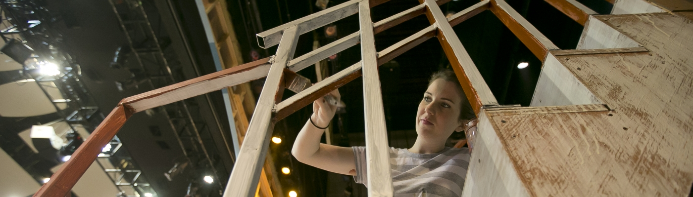 Student Many Goynes painting a set