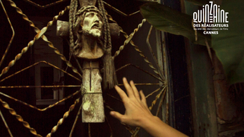 Still of hand reaching toward wooden cross, from ABIGAIL