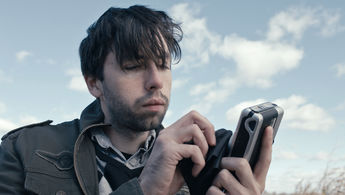Still from film - Man holding device