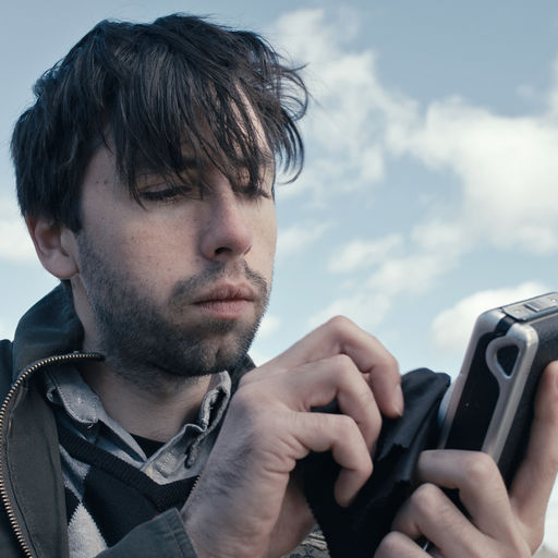 Still from film - Man holding device